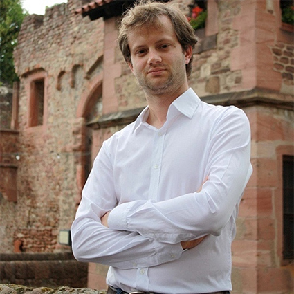 A photo of Axel Kaiser in front of a stone building.