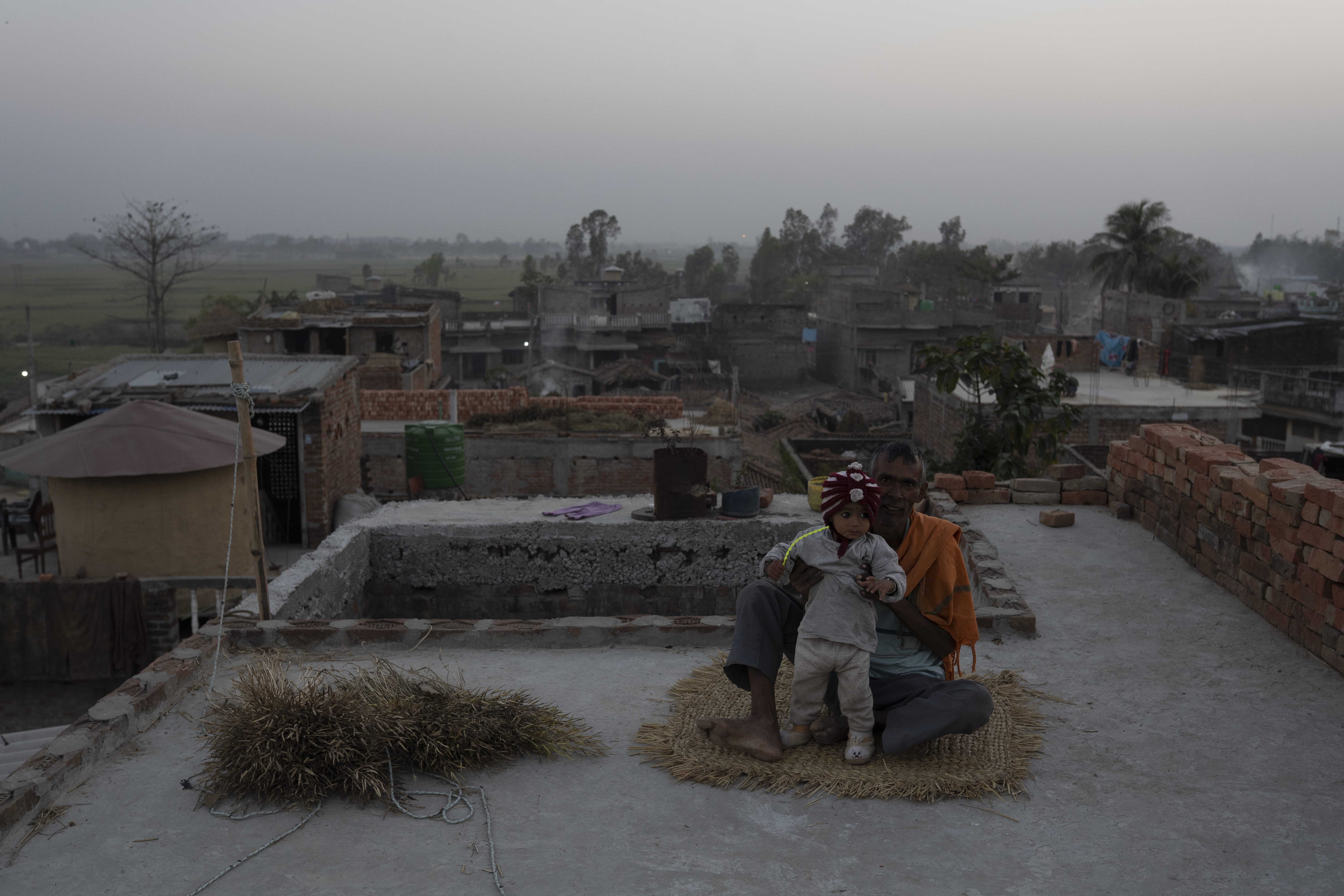 A child sits with a man on a rooftop in Sugauli Birta, an agrarian community near the Indian border of Nepal.