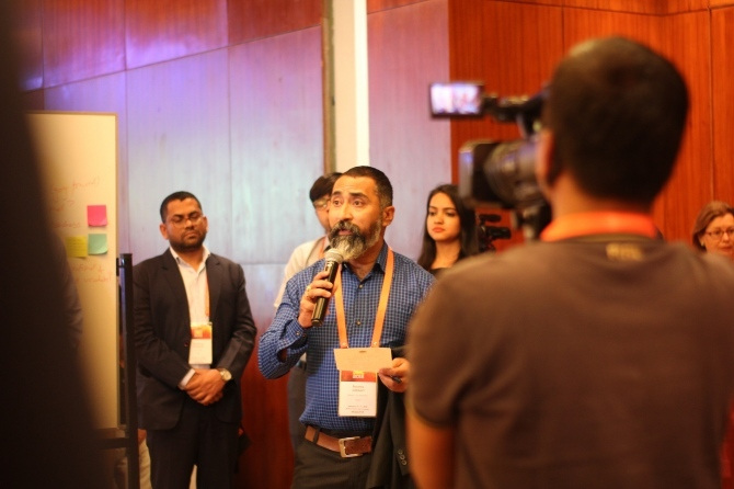 Adhikari speaks as a crowd watches and films him speaking.