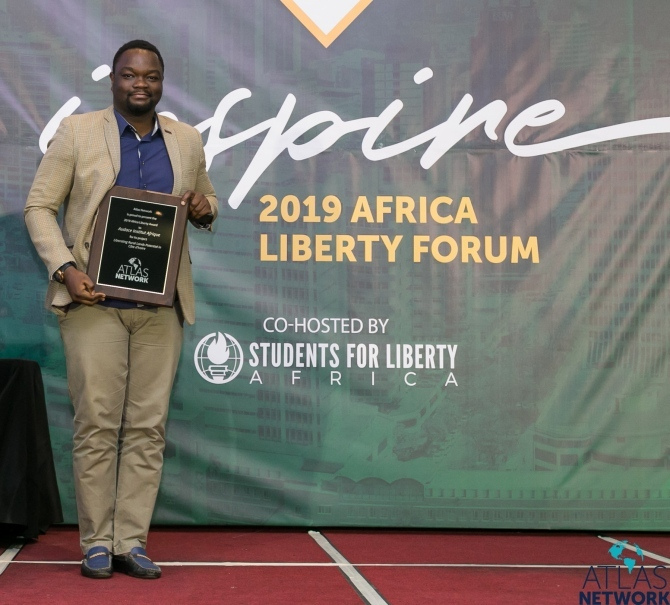A man hold his plaque at the Africa Liberty Forum.