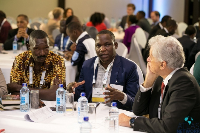 Three men in discussion at a round table at the Africa Liberty Forum.