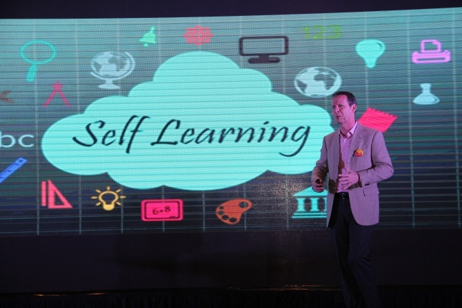"""A man stands before a large graphic with text that says """"Self Learning."""""""