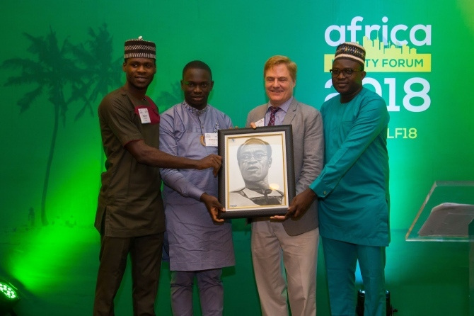 Four men hold a photo of another man at the at the Africa Liberty Forum 2018.