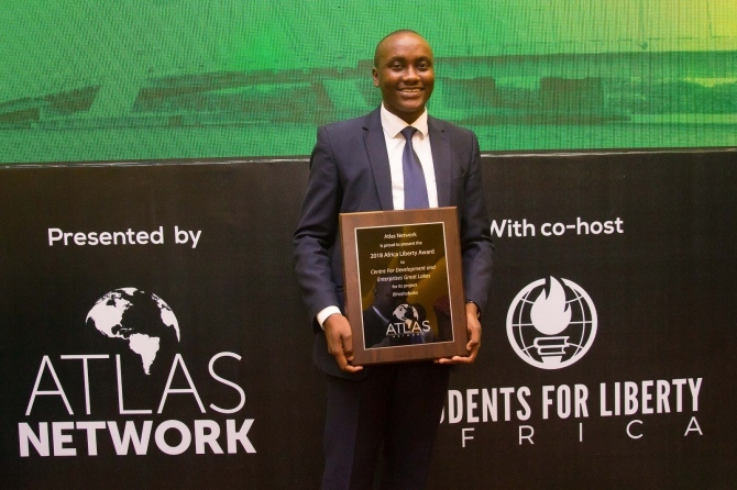 A man proudly holds his plaque at the Students for Liberty Africa event.