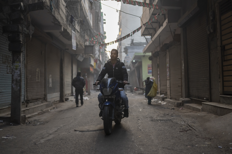 Zubair Ahmed rides his motorcycle to work on a calm Monday morning in Zakir Nagar (AtlasNetwork.org Photo/Bernat Parera).