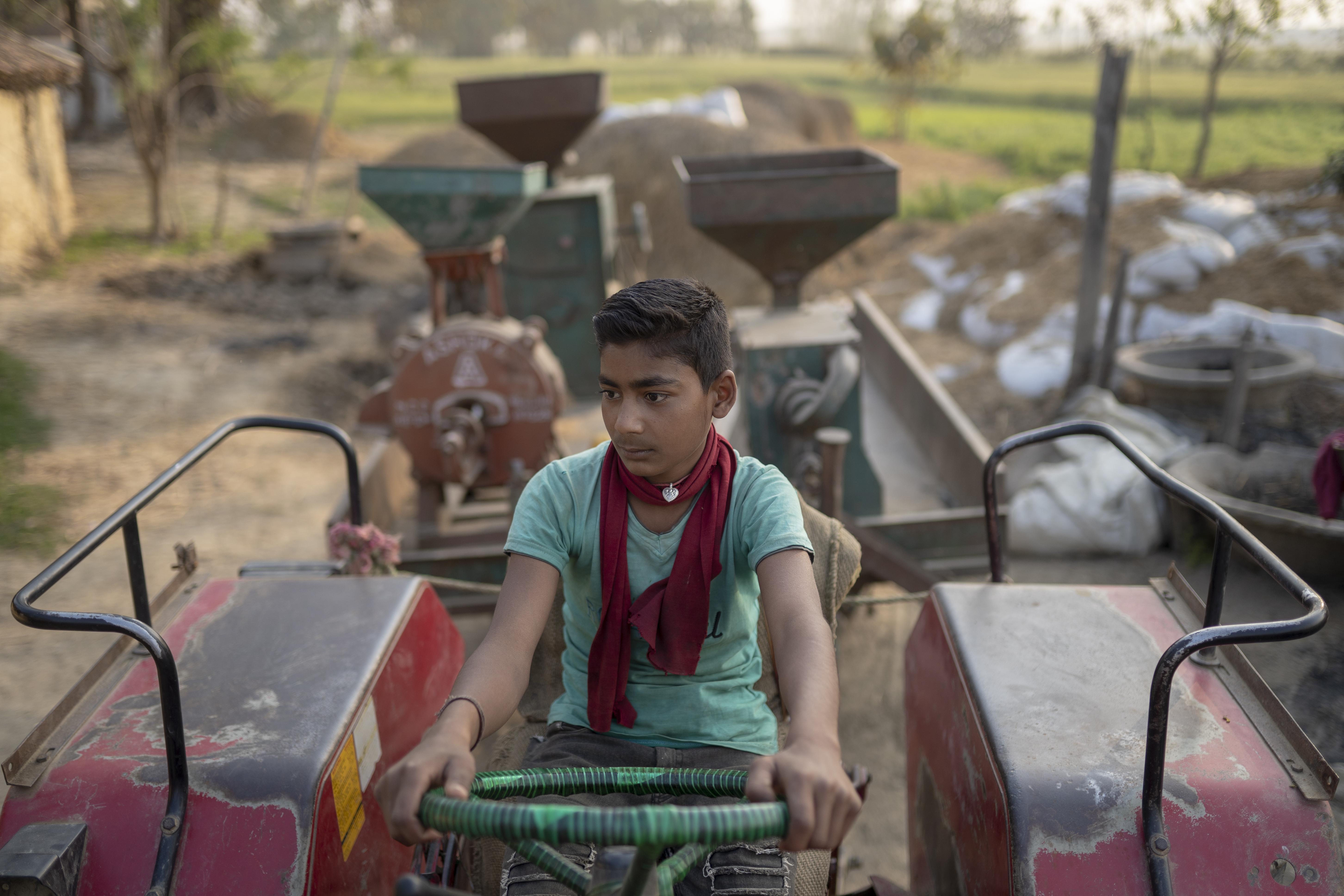 One of Lorik's sons sits atop the mobile mill. (AtlasNetwork.org Photo / Bernat Parera)