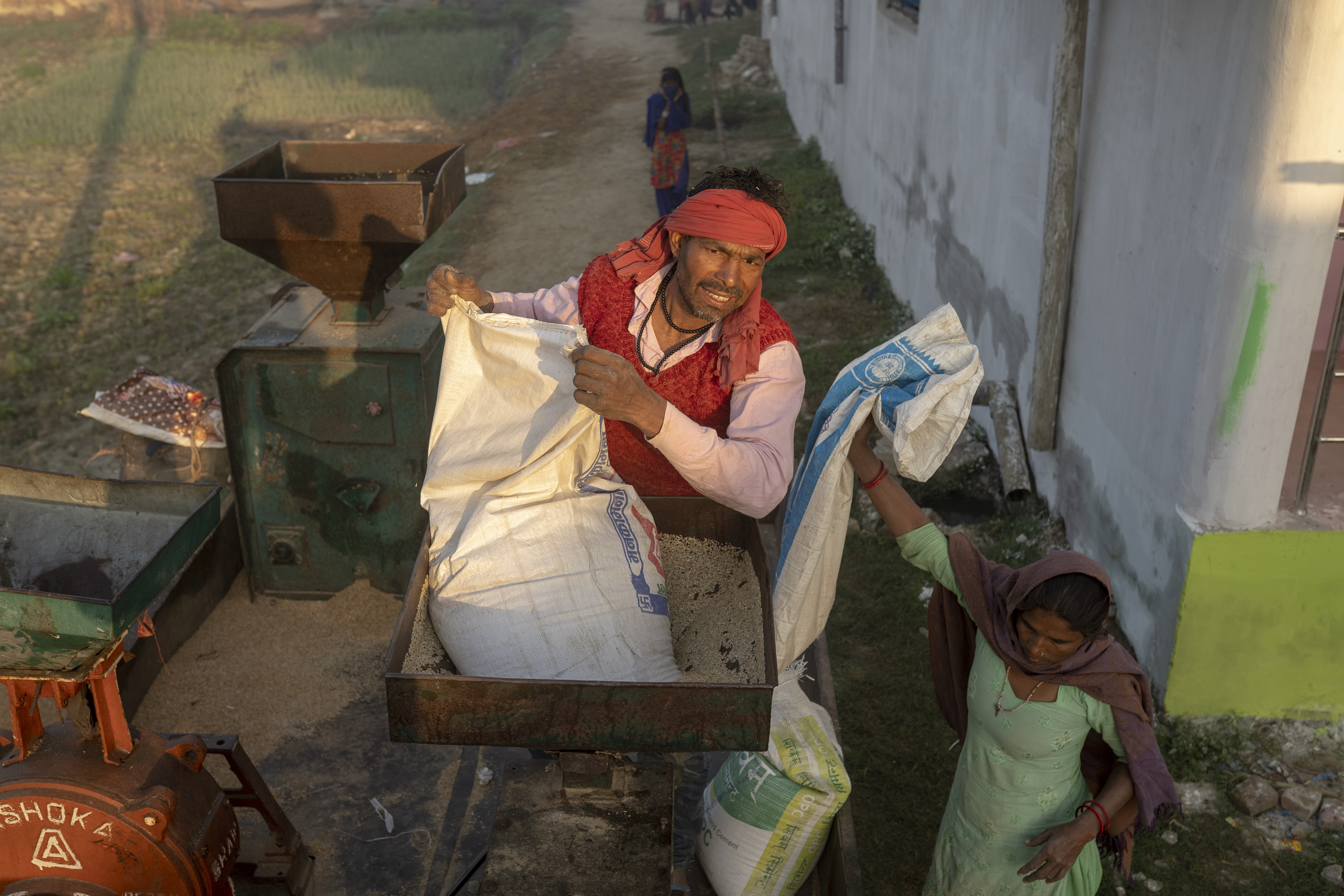 Lorik pours unprocessed rice into a thresher atop his mobile mill. (AtlasNetwork.org Photo / Bernat Parera)
