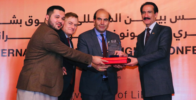 Dr. Tom G. Palmer joins Afghan colleagues in presenting an award for promotion of human rights at the AELSO conference.