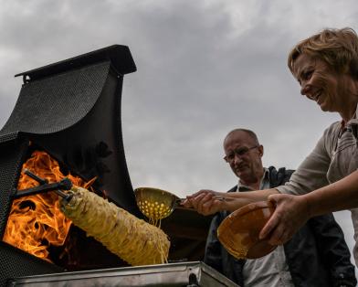 Ona Raudeliūnienė layers batter over a rotating spit during the baking of a traditional šakotis cake (Photo: AtlasNetwork.org/Bernat Parera).