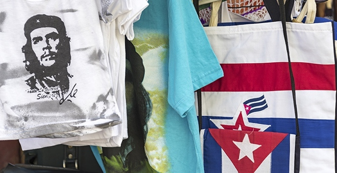 Trinidad, Cuba — February 5, 2016 — Local business kiosk selling Cuban souvenirs like Che Guevara t-shirts, and shopping bags with Cuban flags on the side. Photo: DayOwl / Shutterstock.com