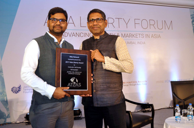 Two men proudly hold a plaque at the Asia Liberty Forum.