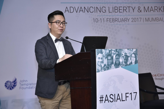 A man delivers a speech at a podium at the Asia Liberty Forum.
