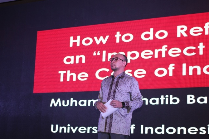 Basri Alf stands on stand with large text on screen behind him.