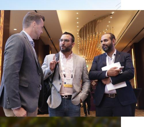 Three Atlas Network partners engaged in a conversation at a conference.