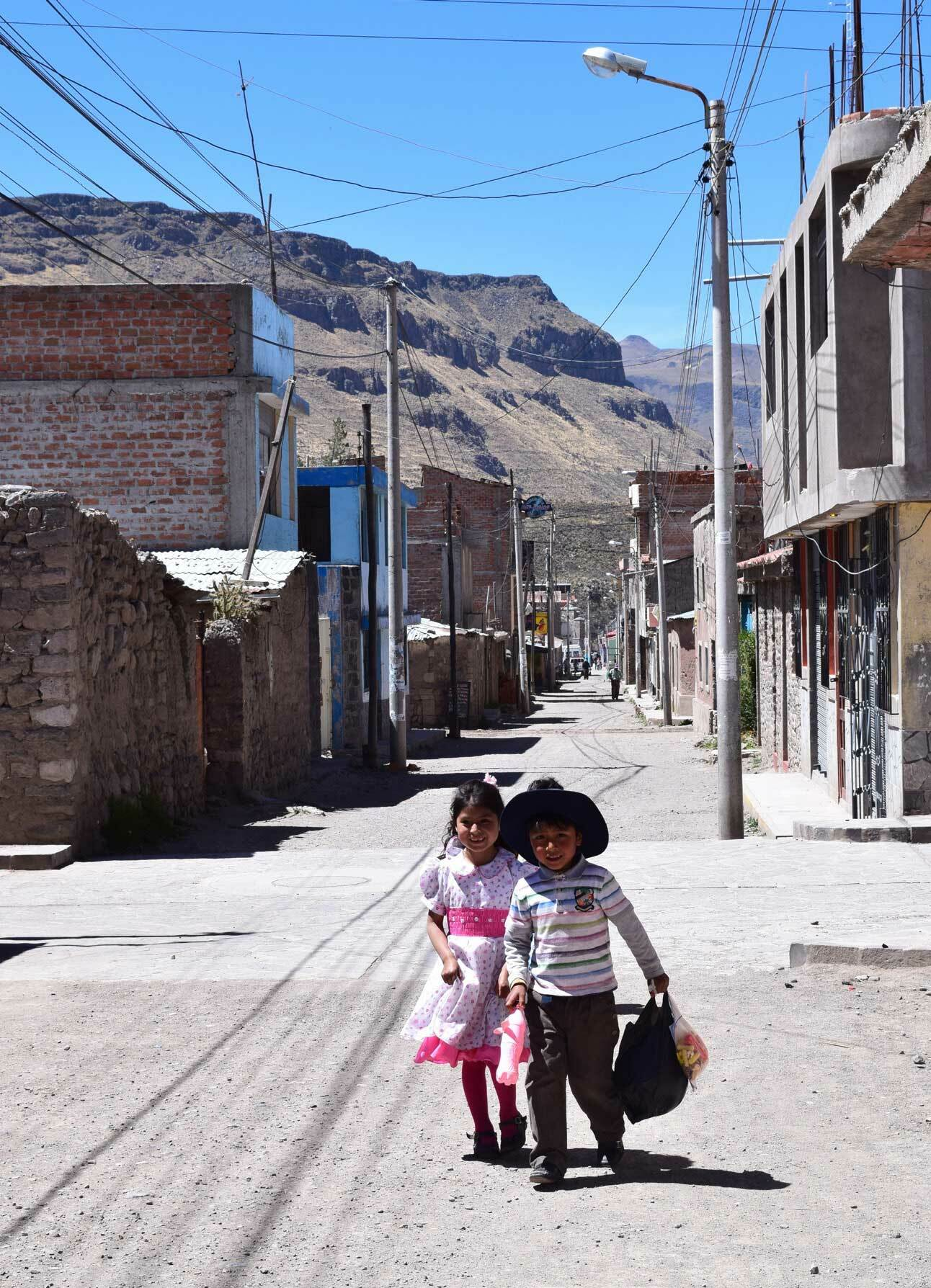 Two children smile as they walk down a narrow village street.