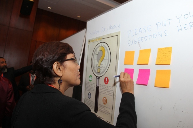 A woman adds thoughts to a sticky note for crowdsourced ideas.