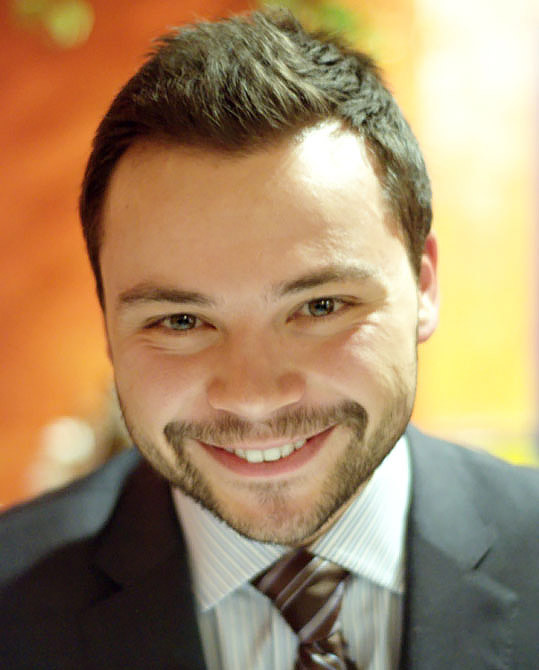 A photo of Diogo costa smiling in full suit and tie.
