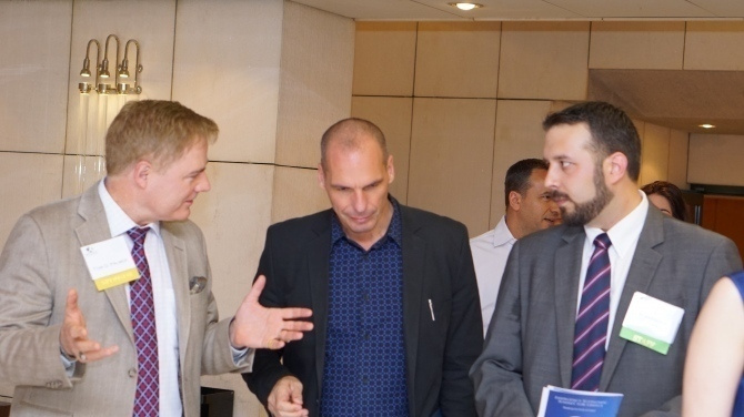 Dr palmer and Yanis Varoufakis walk while in discussion.