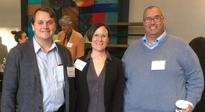 A woman poses for a photo with two men at an Atlas Network event.