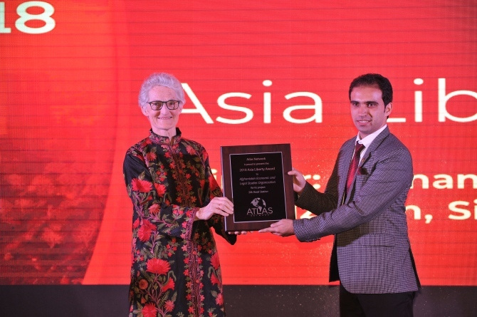 Ramizy holds a plaque on stage at the 2018 Asia Liberty Forum.