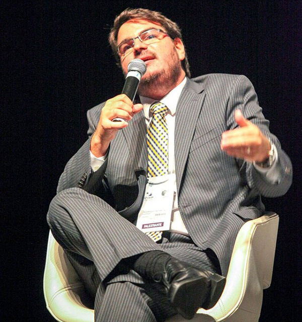 A photo of Rodrigo Constantino speaking at an event while seated and holding a microphone.