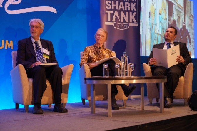 A woman and two men watch intently on stage at the Think Tank Shark Tank.