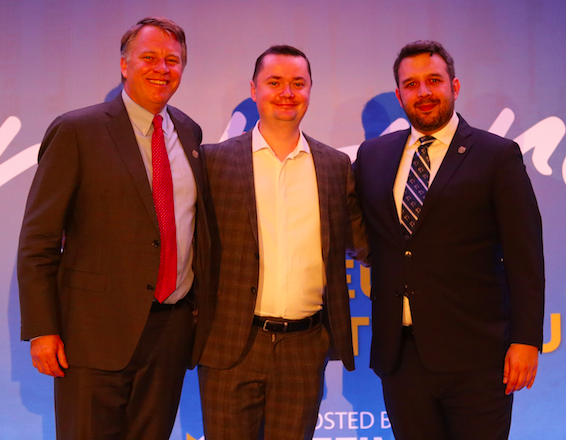 Atlas Network CEO  poses with two men at an event.
