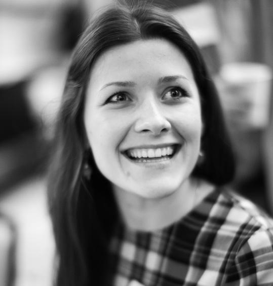 Yuliya Tychkivska smiles for a black and white photo.